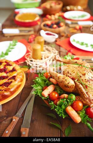 Rôti de dinde aux épices et légumes et autres repas de fête servi sur table Banque D'Images