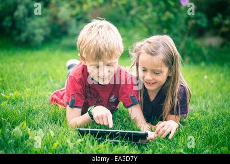 Frère et sœur couchée sur un pré using digital tablet Banque D'Images