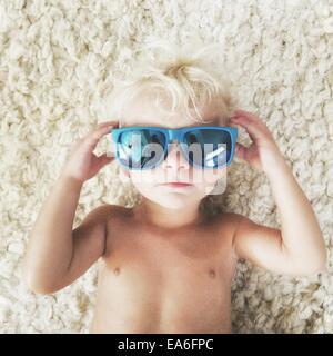 Garçon couché sur un tapis portant des lunettes de soleil Banque D'Images