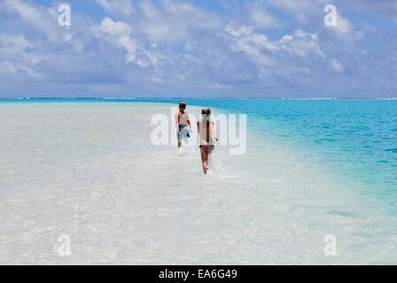 Deux enfants s'exécutant sur barre d'où l'océan, Aitutaki, Îles Cook Banque D'Images