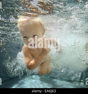 Boy swimming underwater in a swimming pool Banque D'Images