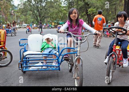 Enfants philippins la bicyclette à Burnham Park, Baguio City, Philippines. Une jeune fille vélo randonnées avec Banque D'Images