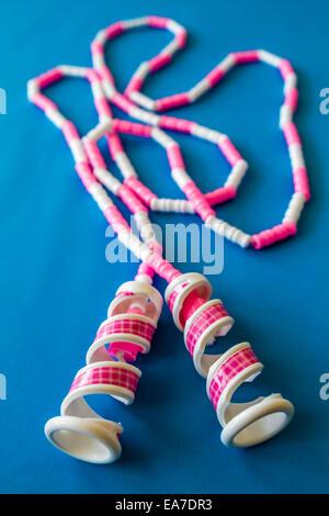 Rose et blanc jouet corde à sauter sur un fond bleu Banque D'Images