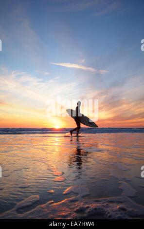 Low angle view of surfer avec une planche de surf à marcher le long bord de l'eau pendant le coucher du soleil Constantine Banque D'Images