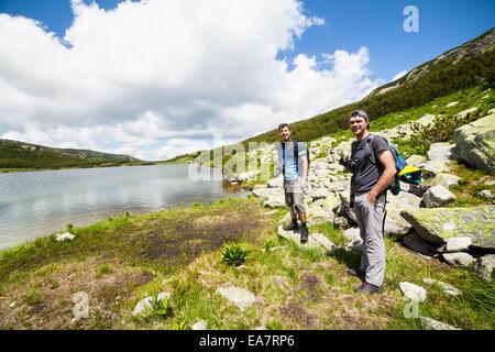 Deux randonneurs de race blanche avec des sacs de marcher autour d'un lac dans les montagnes Banque D'Images