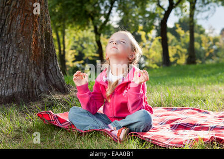 Little girl relaxing in yoga pose sur l'herbe dans un parc Banque D'Images