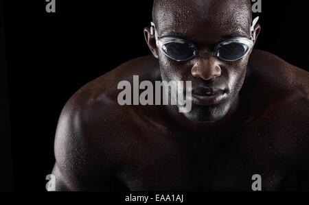 Portrait d'un jeune homme africain portant des lunettes de natation isolé sur fond noir. Mettre en place jeune athlète.