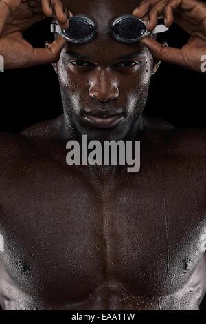 Gros plan du nageur déterminés à l'aide de lunettes à la recherche à l'appareil photo. Jeune homme africain avec Banque D'Images