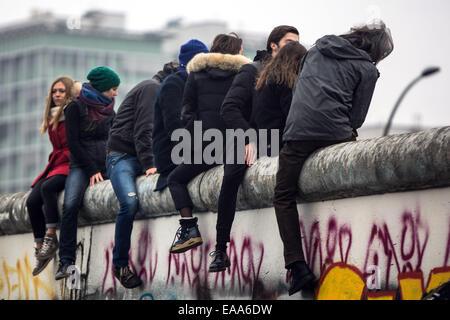 Berlin, Allemagne. 09Th Nov, 2014. Les jeunes gens assis sur le mur de Berlin à l'East Side Gallery à l'occasion Banque D'Images