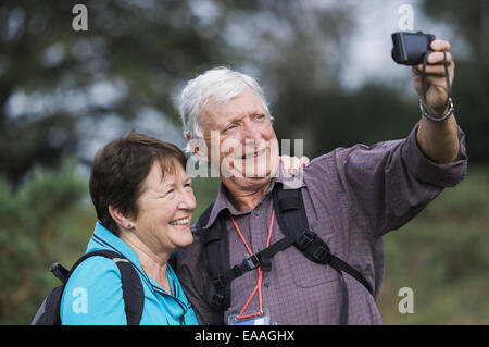 A mature couple taking a photograph selfy tandis que dehors la marche. Banque D'Images