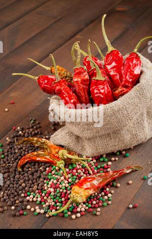 Piment rouge dans un sac en toile sur la table en bois Banque D'Images