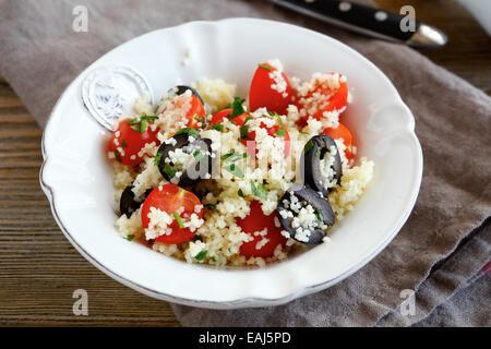Délicieuse salade couscous aux légumes et olives sur une assiette, Close up Banque D'Images
