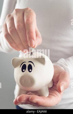 Woman putting coins in piggy coin bank, selective focus avec profondeur de champ Banque D'Images