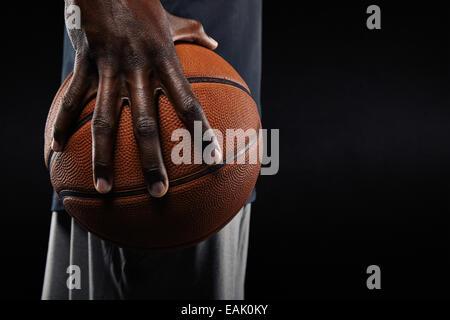 Close-up of a hand-ball joueur tenant une boule sur fond noir.