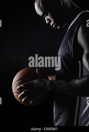 Vue latérale du jeune sportif africain holding basketball sur fond noir. Joueur de basket-ball. Banque D'Images