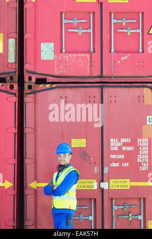 Worker smiling près de conteneurs de fret Banque D'Images
