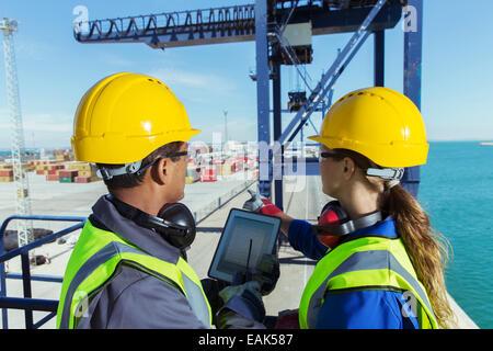 Les travailleurs utilisant tablette numérique sur grue de chargement Banque D'Images