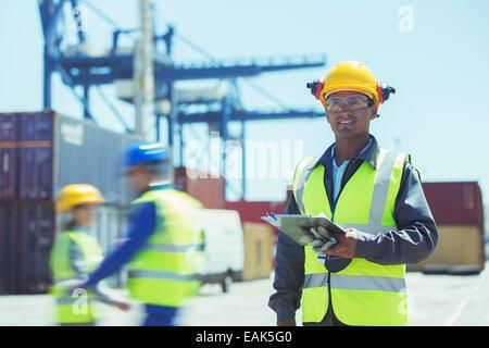 Worker près de conteneurs de fret Banque D'Images