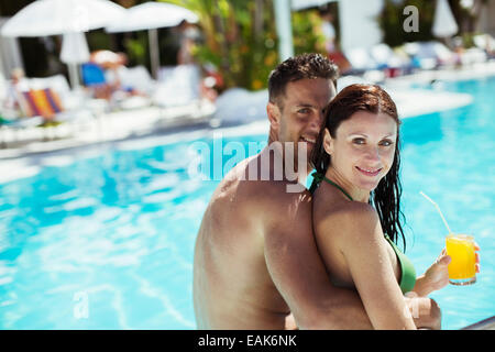 Portrait of smiling couple sitting by resort piscine Banque D'Images