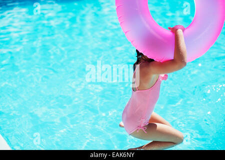 Fille avec anneau gonflable rose jumping into swimming pool Banque D'Images
