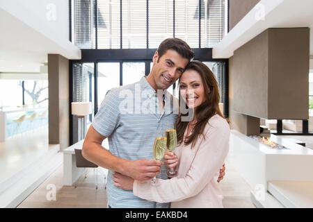 Portrait of smiling woman holding champagne flutes et in modern living room Banque D'Images
