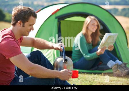 Couple boisson chaude tout en camping à la campagne Banque D'Images