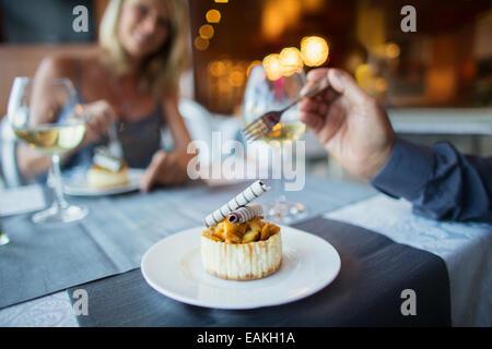Couple eating dessert au restaurant chic Banque D'Images