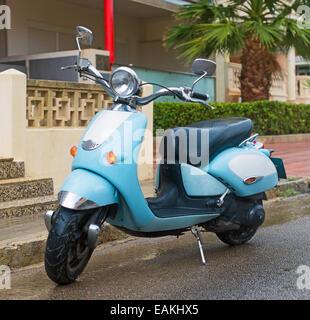 Scooter bleu garée dans la rue.