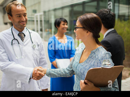 Smiling doctor shaking hand with woman in front of hospital Banque D'Images
