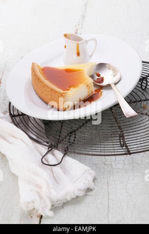 Gâteau au fromage classique sauce caramel et sur la plaque sur bleu texture background Banque D'Images
