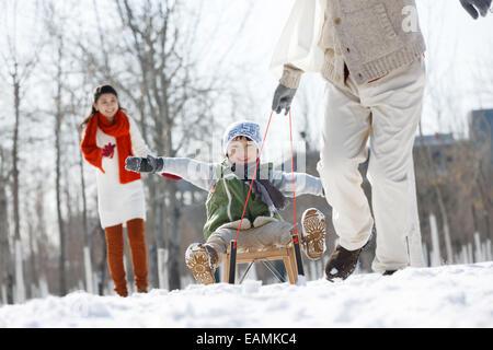 La famille orientale jouer dans la neige Banque D'Images