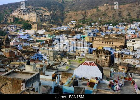 L'Inde, Rajasthan, Mewar, Bundi, Palais de la ville en arrière-plan, les femmes sur le toit de la vieille ville avec la maison bleue