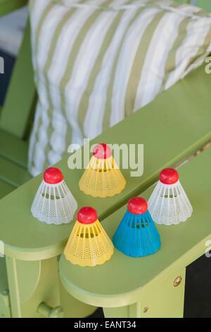 Badminton birdies colorés assis sur chaise adirondack vert coussin à rayures avec bras Banque D'Images