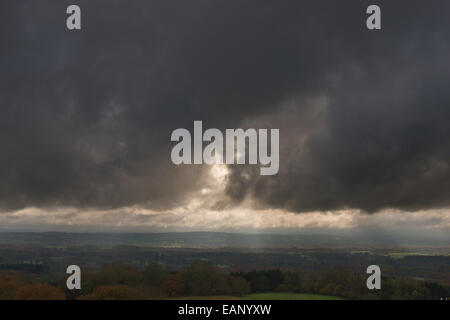 Des arbres du soleil soleil pénétrer à travers les nuages de pluie menaçante sombre planant au-dessus de High Weald Ashdown Forest dans la distance