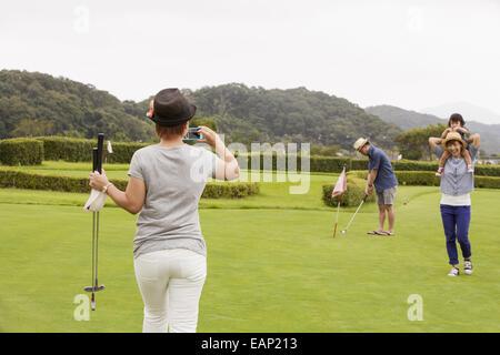 Sur un terrain de golf de la famille.Un enfant et trois adultes. Une femme avec un appareil photo.
