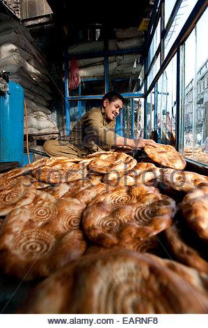 Un homme fait du pain naan dans une stalle à Kaboul. Banque D'Images