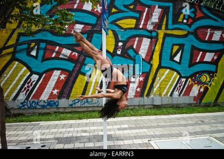 Un danseur effectue une pose sur un poteau en plein air à côté d'un graffiti urbain. Banque D'Images