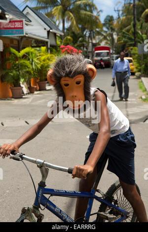 L'Ile Maurice, Grand Baie, enfant portant masque singe tout en riding bicycle Banque D'Images