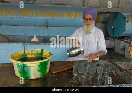 Un Sikh verse de l'eau potable fraîche dans des verres. Banque D'Images