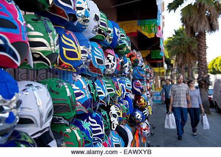 Shoppers passant par un stand vendant des masques de catch mexicain, qui servent de rappels colorés de l'influence Banque D'Images
