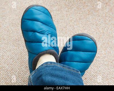 Une femme avec les pieds croisés portant une paire de jeans et des chaussons rembourrés sur le tapis à la maison Banque D'Images