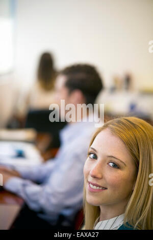 Woman working in office, smiling Banque D'Images