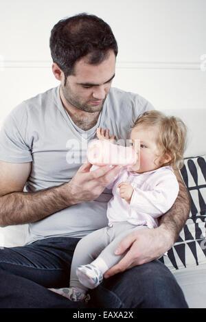 Père holding baby girl on lap, nourrit sa bouteille Banque D'Images