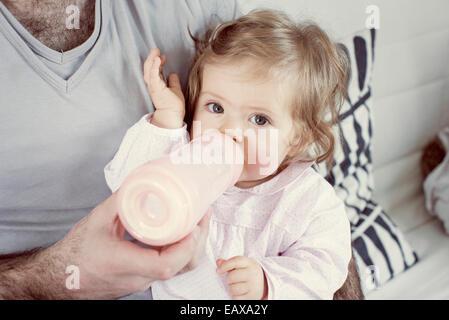 Bébé fille 6-7, boire de la bouteille, cropped Banque D'Images