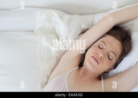Woman Lying in Bed stretching arms over head Banque D'Images