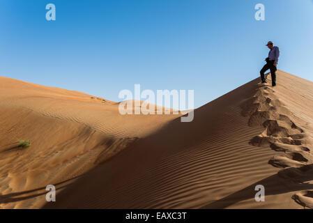 Un homme avec une caméra debout sur une dune de sable dans le désert d'Oman. Banque D'Images