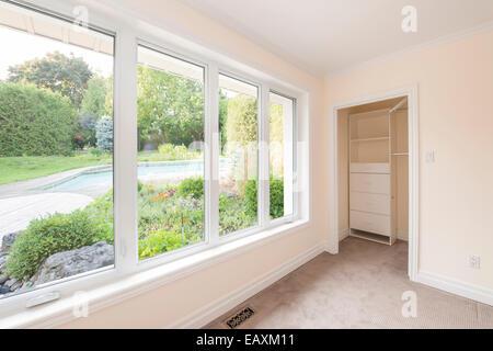 Grande fenêtre dans une chambre vide à l'été sur cour avec jardin et piscine résidentielle Banque D'Images