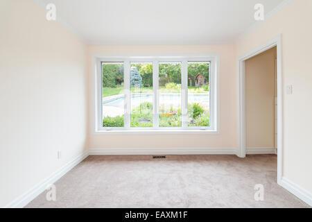 Salle vide avec une grande fenêtre sur cour et l'été à la piscine résidentielle Banque D'Images