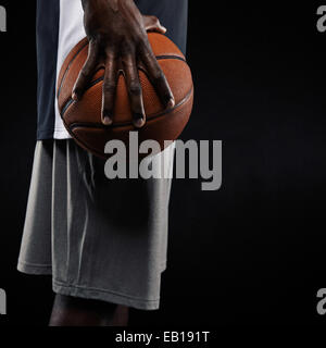 Portrait of a young man holding basketball sur fond noir. Mid section image de joueur de basket-ball de l'Afrique.