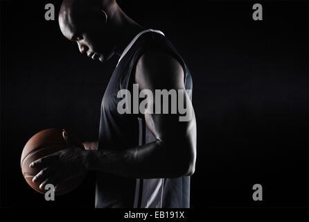 Vue latérale du fit young basketball player holding ball sur fond noir avec l'exemplaire de l'espace. Jouer au basket Banque D'Images